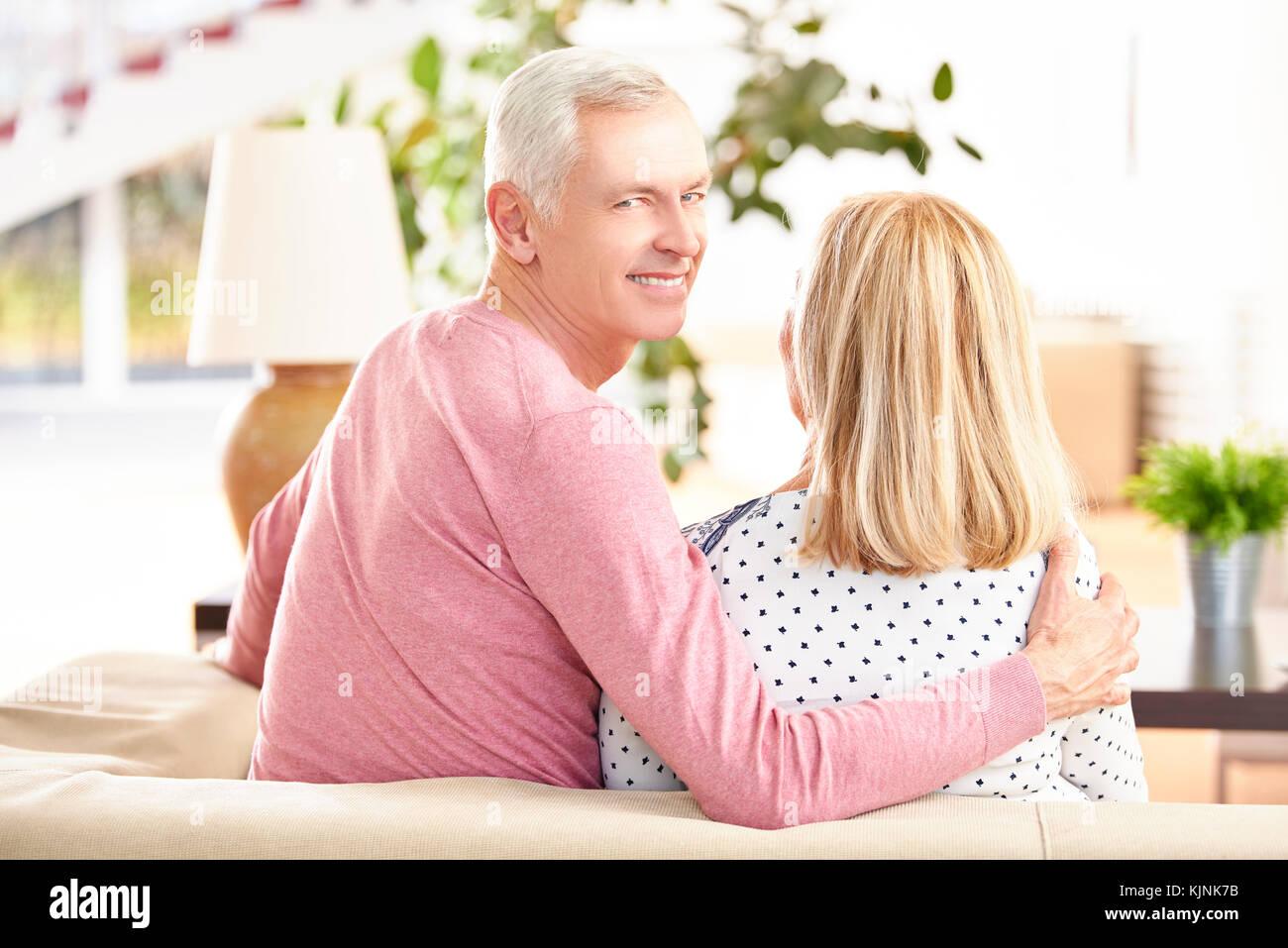 Vue arrière Vue d'un senior couple sitting on sofa at home alors qu'un homme âgé à l'arrière et de sourire. Banque D'Images