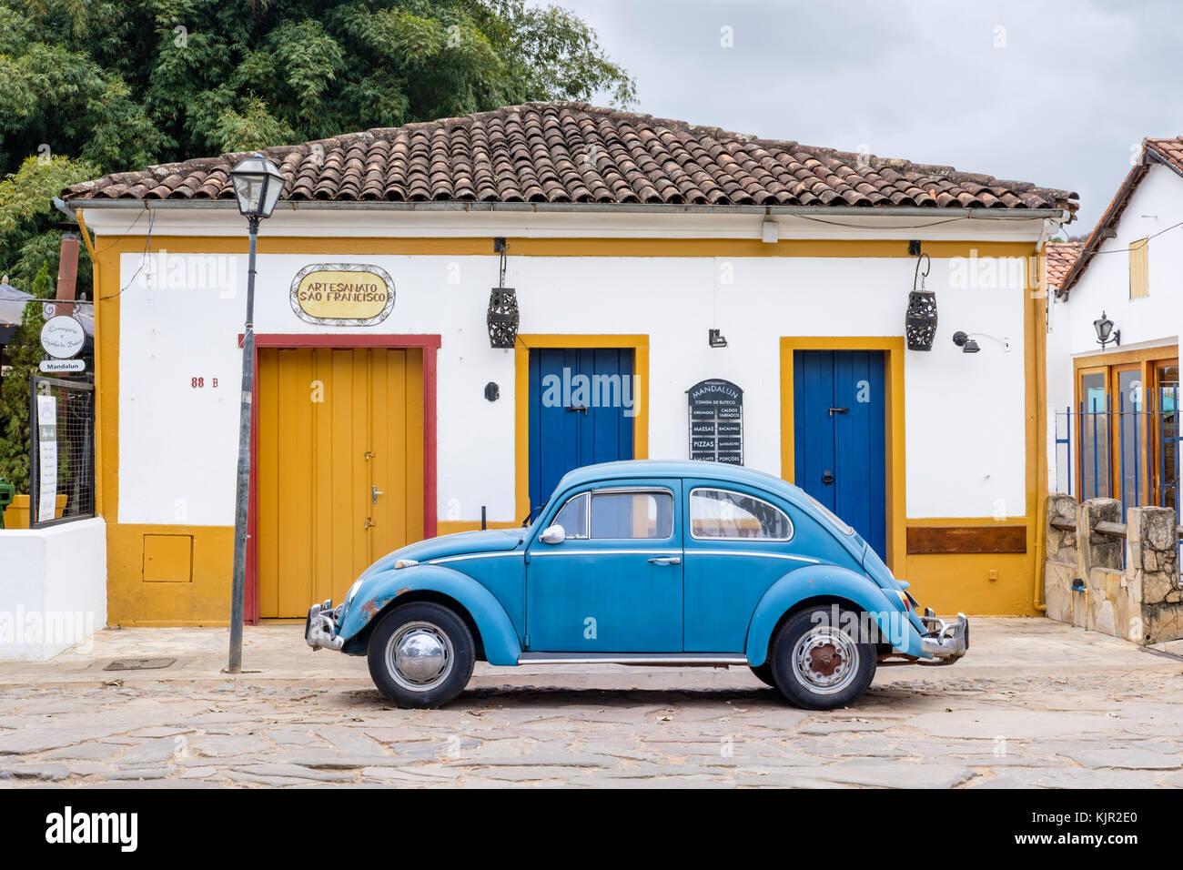 Maison coloniale jaune, bleu coccinelle Volkswagen, rue pavée, Tiradentes, Minas Gerais, Brésil. Banque D'Images
