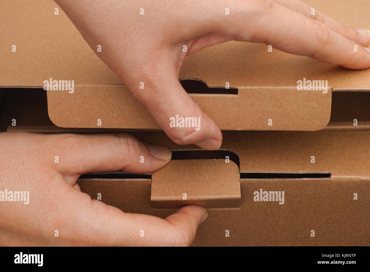 Personne mains l'ouverture d'une boîte en carton. close-up. Photo Stock