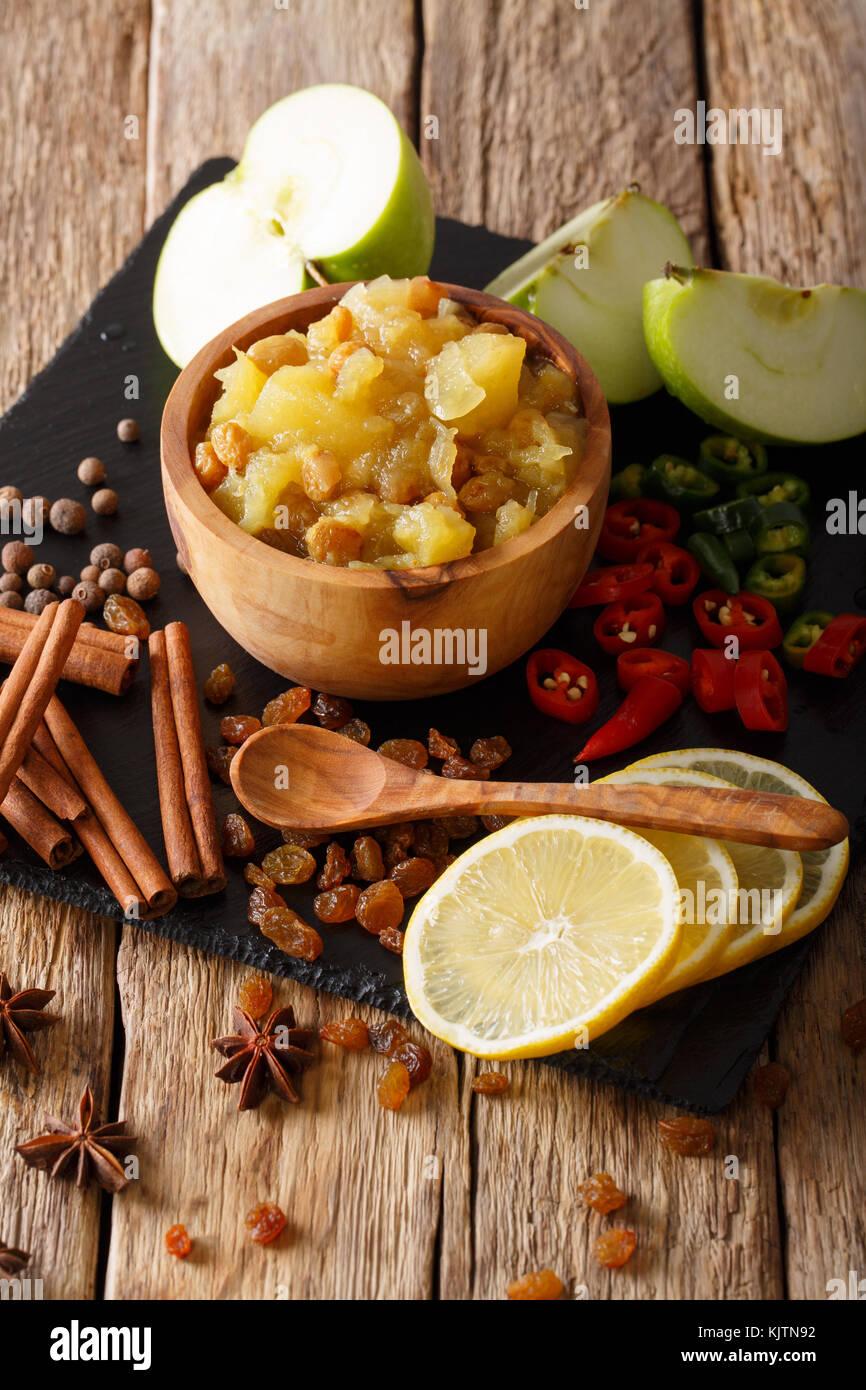 Chutney de pommes maison avec des raisins secs et d'épices close-up dans un bol sur la table verticale. Photo Stock