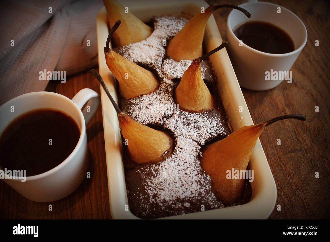 Gâteau de pain au chocolat avec des poires entières cuites à l'intérieur et deux tasses Photo Stock