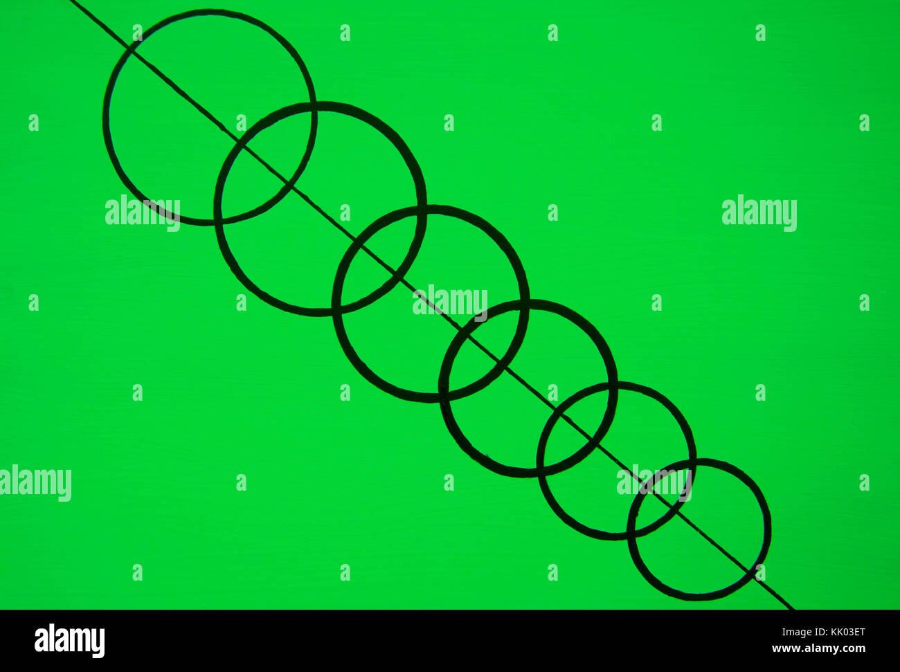 Les cercles noirs liés entre eux sur la ligne noire avec un fond vert Photo Stock
