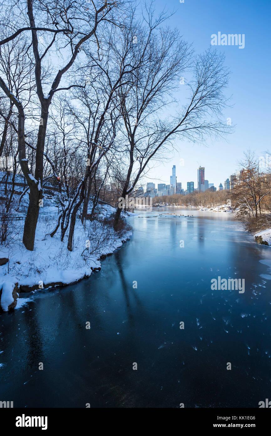 Vue hivernale de Central Park depuis le lac gelé avec le paysage urbain de l'upper west side à Manhattan, Photo Stock