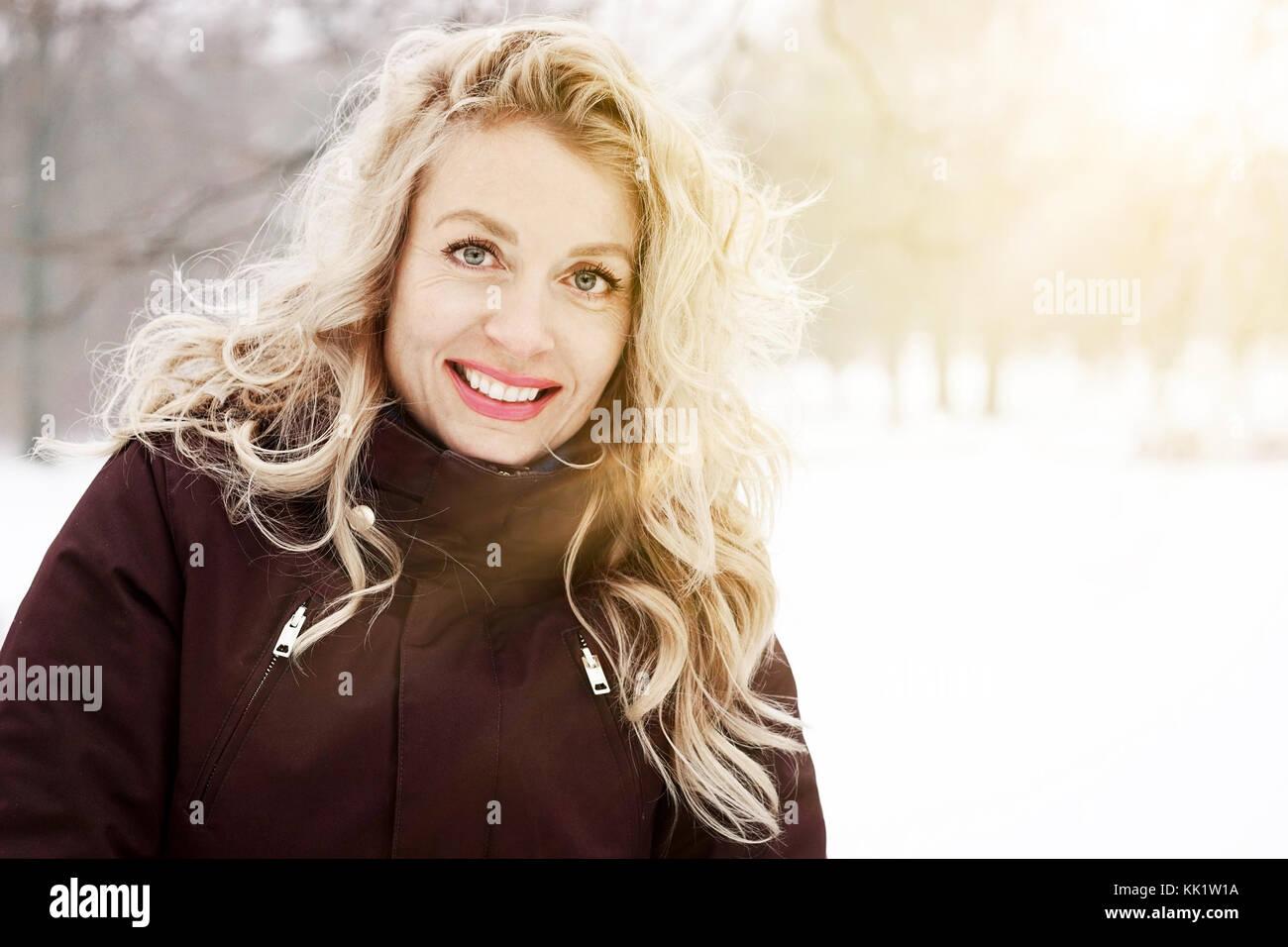 Femme blonde en paysage d'hiver avec sun flare Banque D'Images