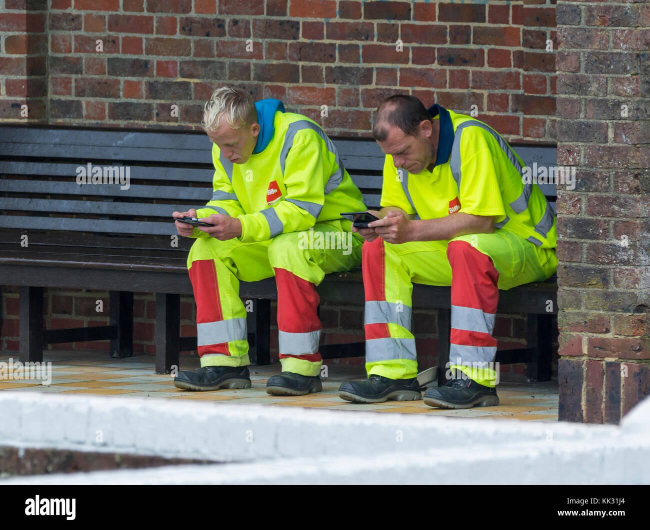 Paire d'ouvriers hommes assis en faisant une pause pendant l'utilisation de téléphones mobiles. Photo Stock