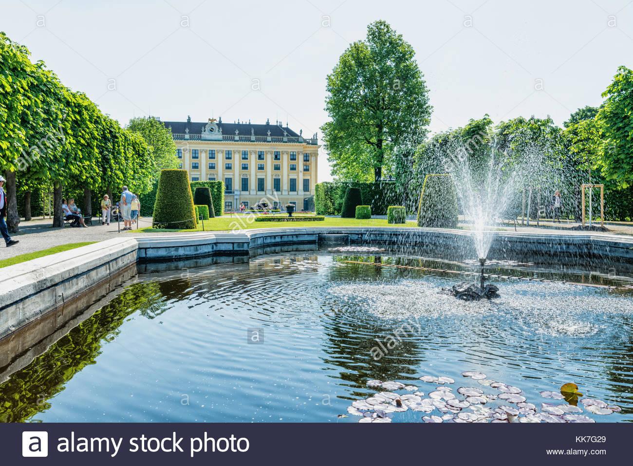 Les touristes vienne à une belle fontaine du jardin du palais de Schönbrunn à la lumière du Photo Stock