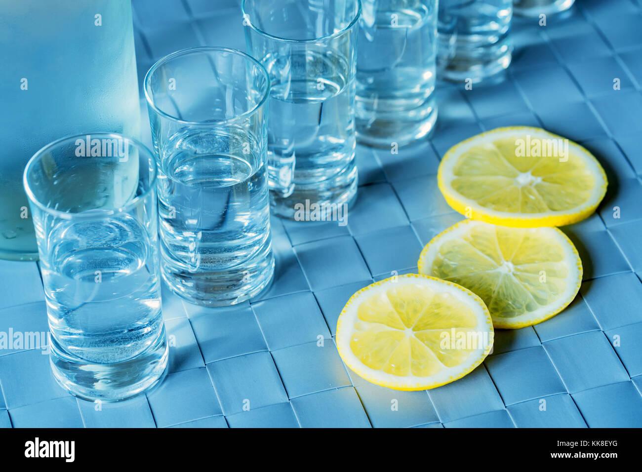 Verre de vodka et citron sur la surface bleue Banque D'Images