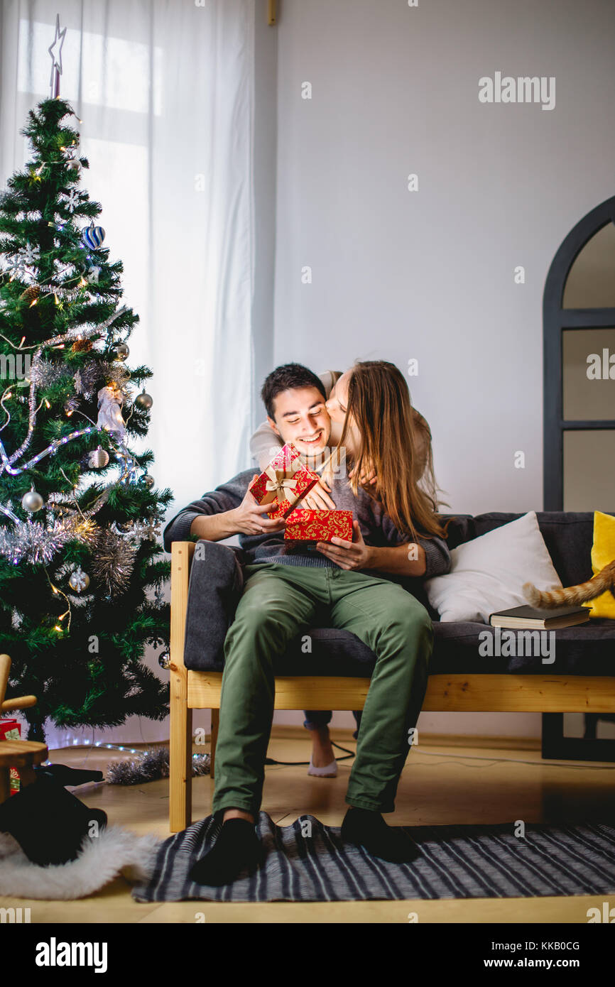 L'homme de l'ouverture d'une boîte-cadeau tandis que sa copine assis près d'elle sur la table Banque D'Images