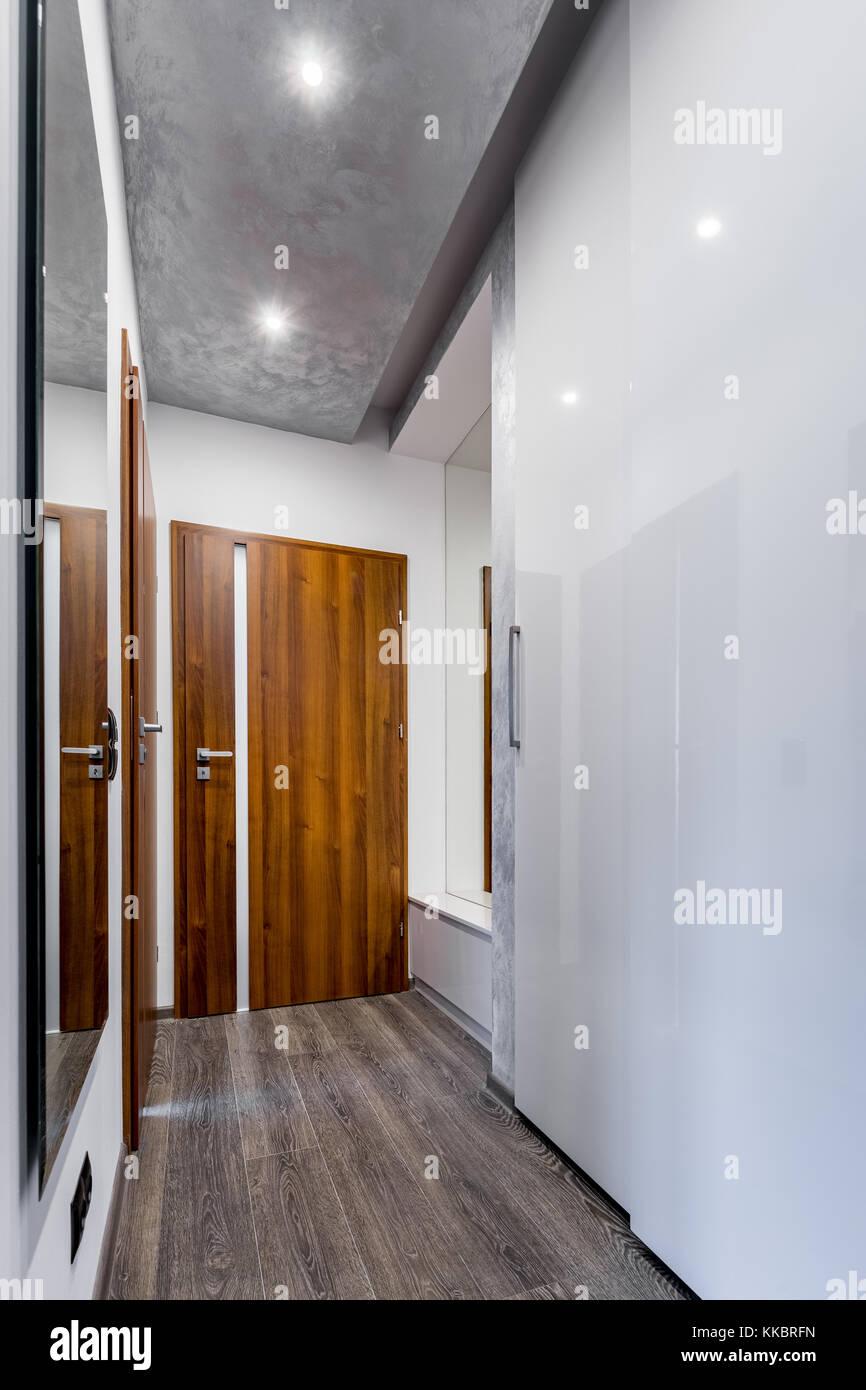 entrée élégante avec porte en bois, armoire blanche et grand miroir