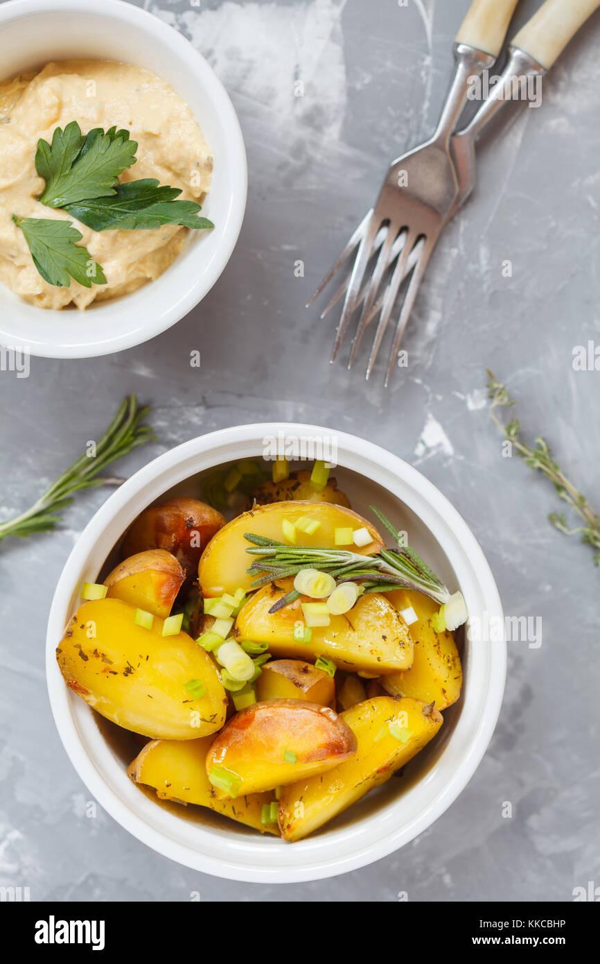 Pommes de terre au four au romarin et l'oignon vert en forme de céramique blanche d'hummus, vue du dessus, fond Banque D'Images