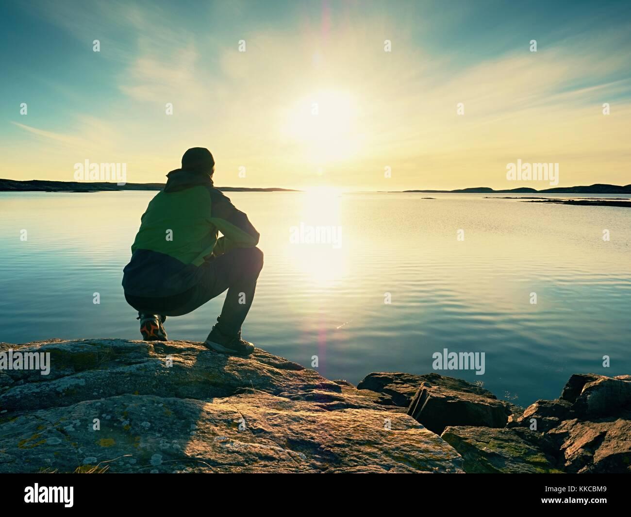 Homme fatigué s'asseoir sur la côte rocheuse. Plan d'eau calme, Rocky Island et fond de ciel coucher Photo Stock