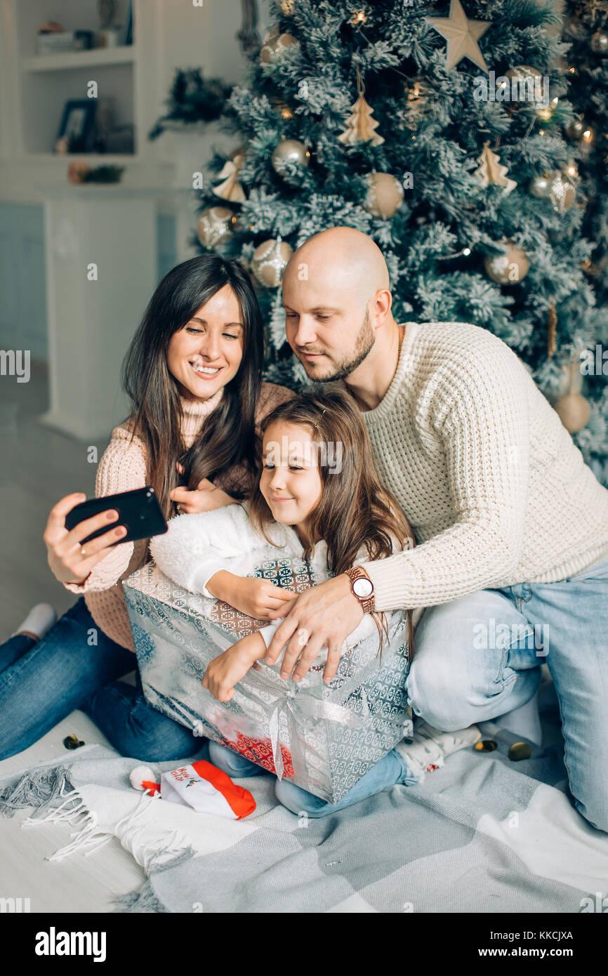 Famille de quatre jeunes heureux de prendre une photo d'eux-mêmes par une cheminée Photo Stock