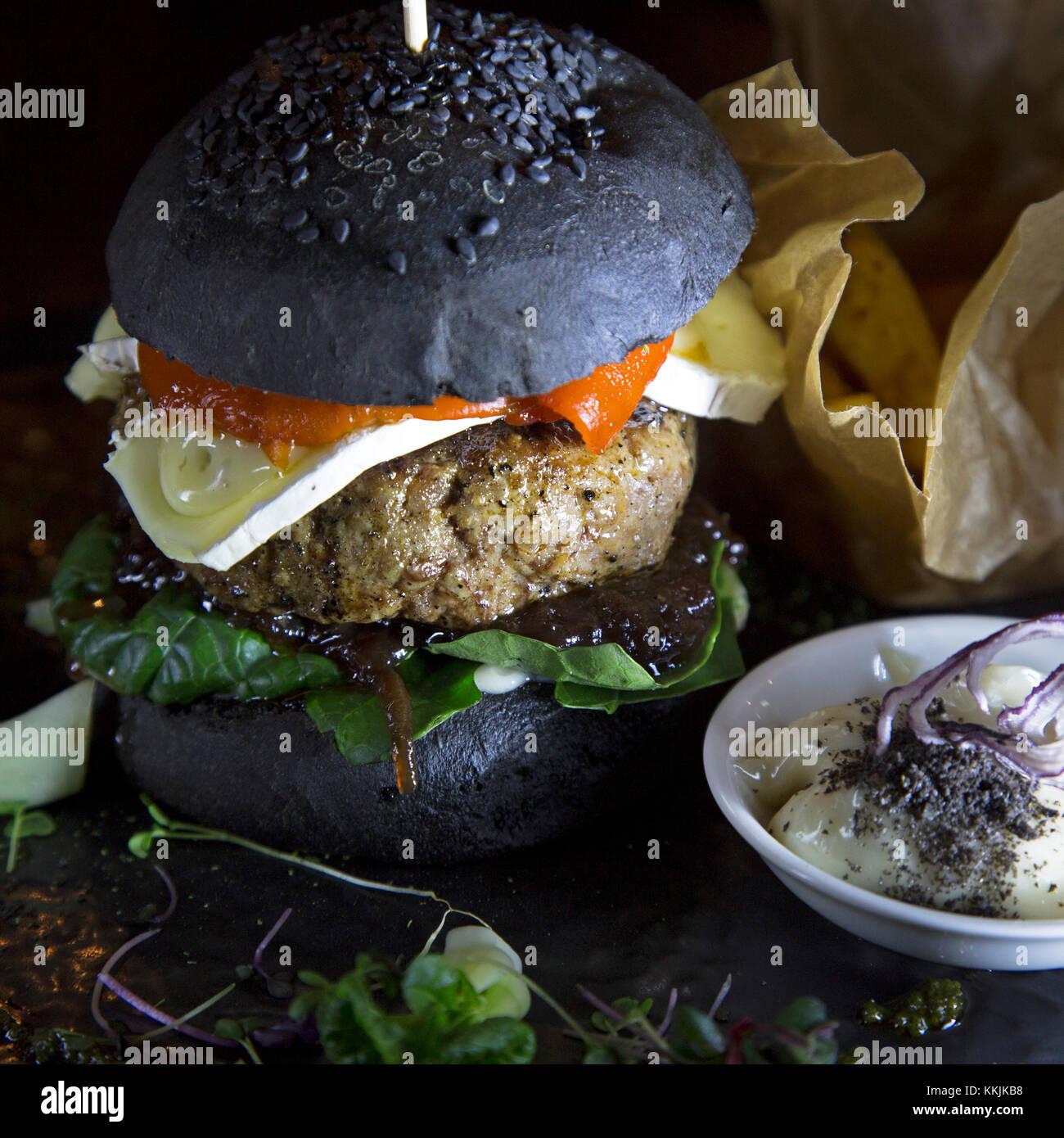 Hamburger d'agneau servi avec pain noir dans un bun au restaurant sourdine à Riga, Lettonie. Le burger dispose d'une tranche de fromage français. Banque D'Images