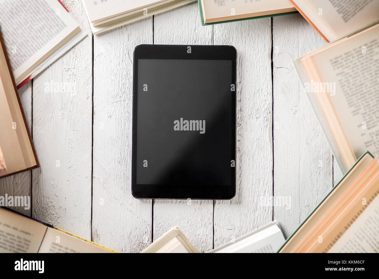 Ebook Reader noir avec beaucoup de livres en papier Banque D'Images
