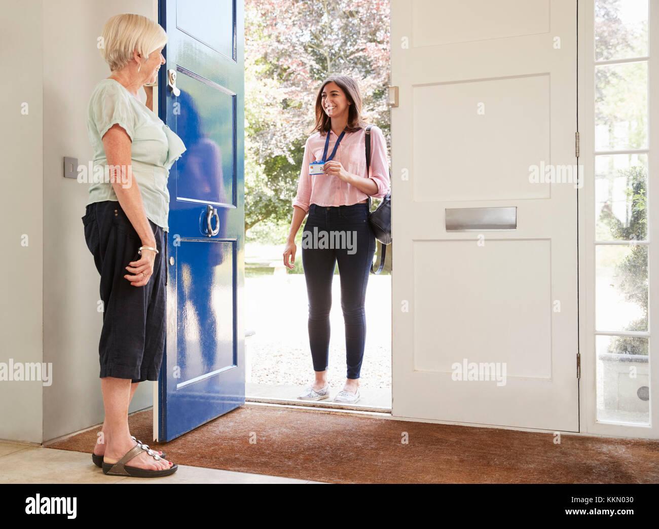 Senior woman ouvre la porte à des travailleurs de sexe féminin sur