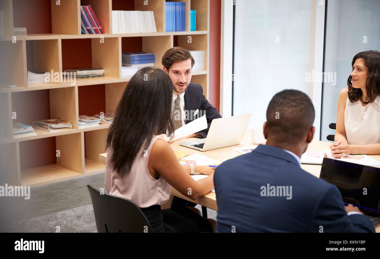 Quatre personnes à une salle de réunion Photo Stock