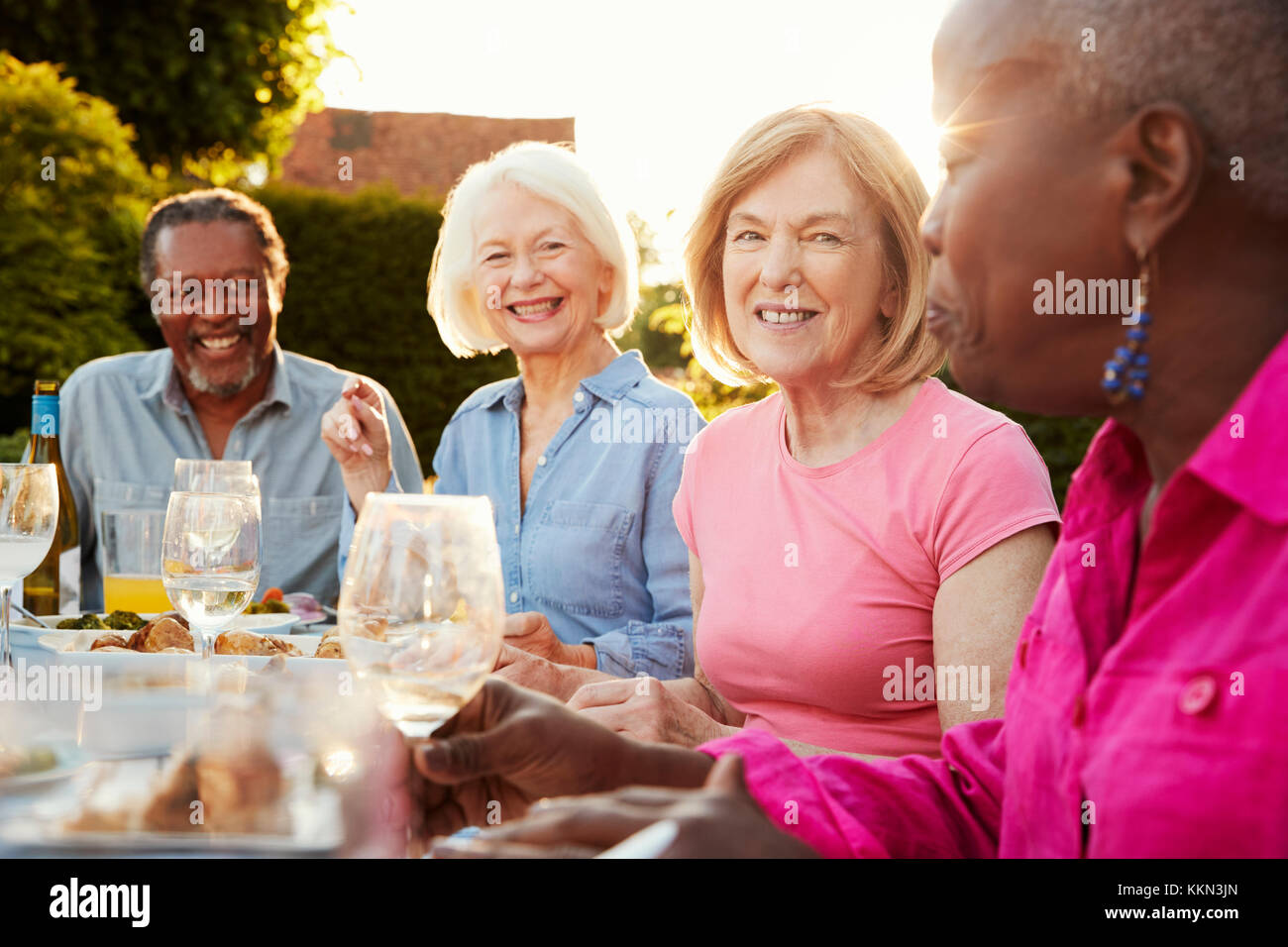 Groupe de hauts friends enjoying outdoor dinner party at home Photo Stock