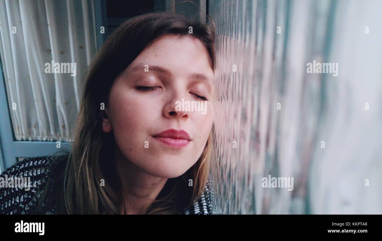 Jeune femme à la maison en face d'une fenêtre Photo Stock