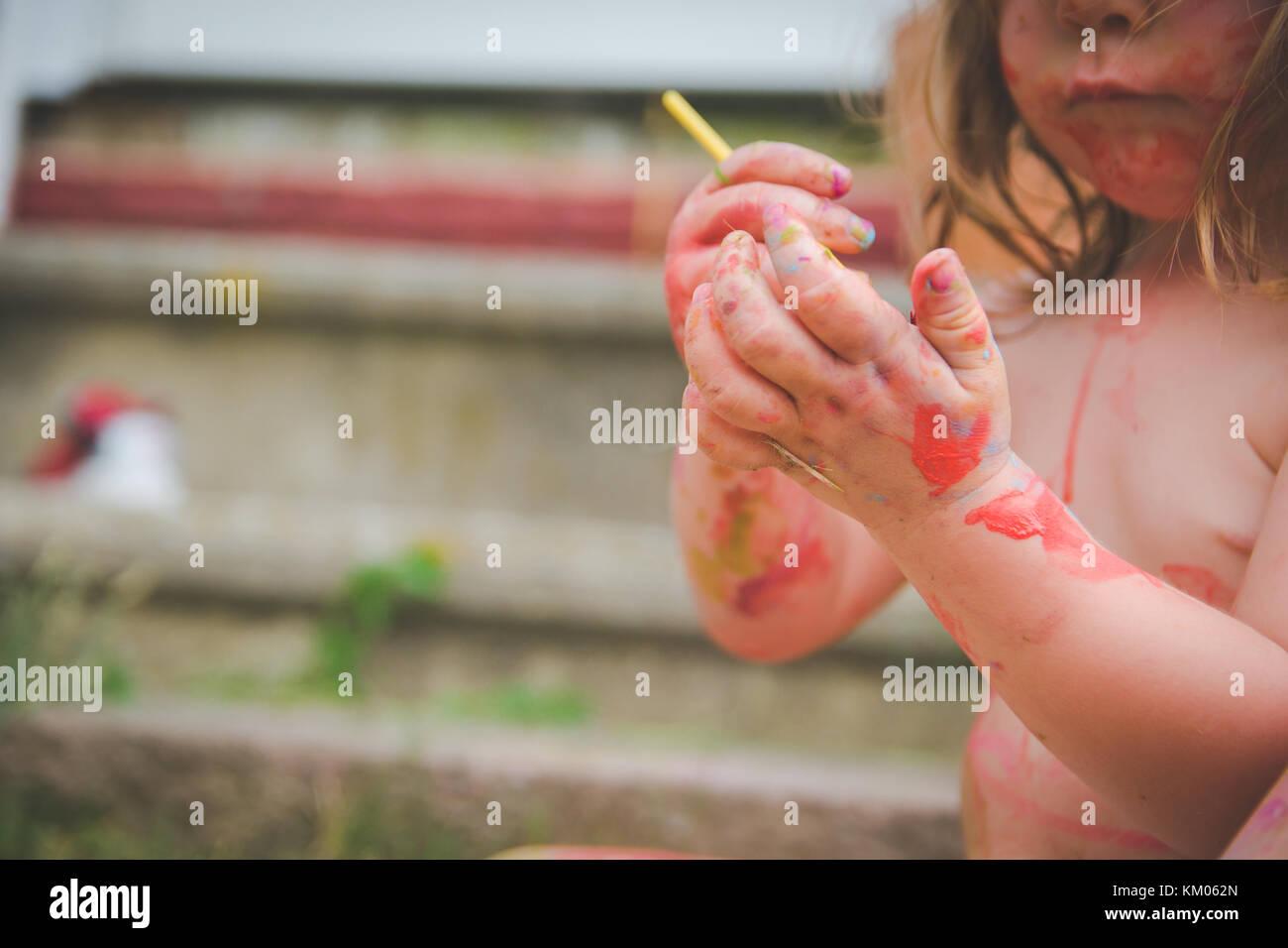 Les peintures d'un tout-petit sur ses mains. Photo Stock