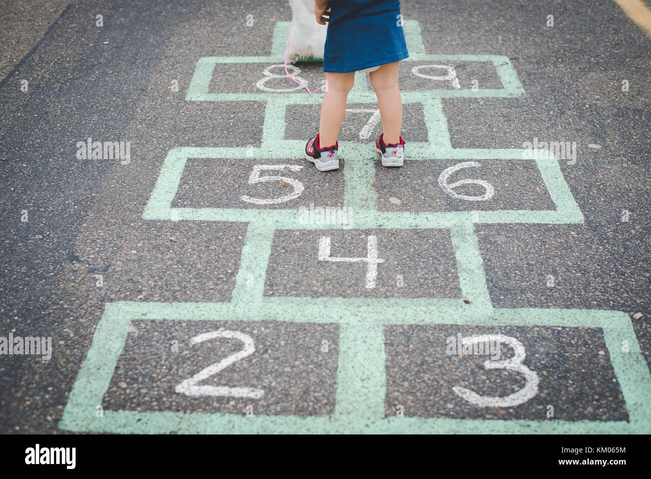Un enfant se tient sur une marelle, jeu de l'enfant, dans un terrain de stationnement. Photo Stock
