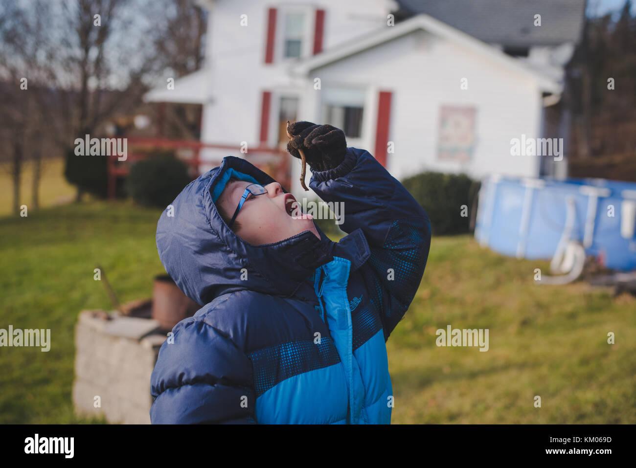 Un garçon fait semblant de manger un ver. Photo Stock