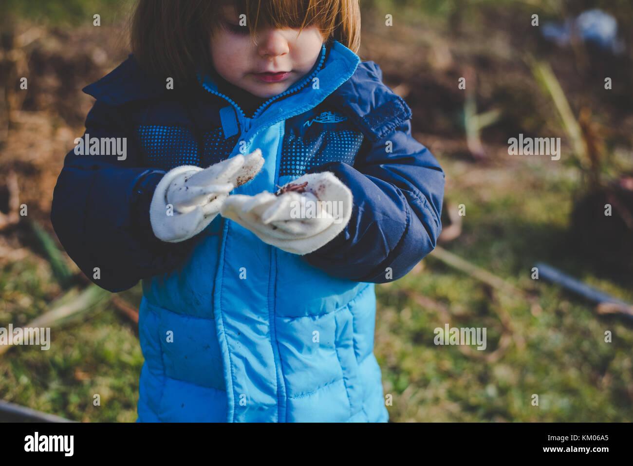 Une petite fille à la saleté à dans ses mains couvertes de gants Photo Stock