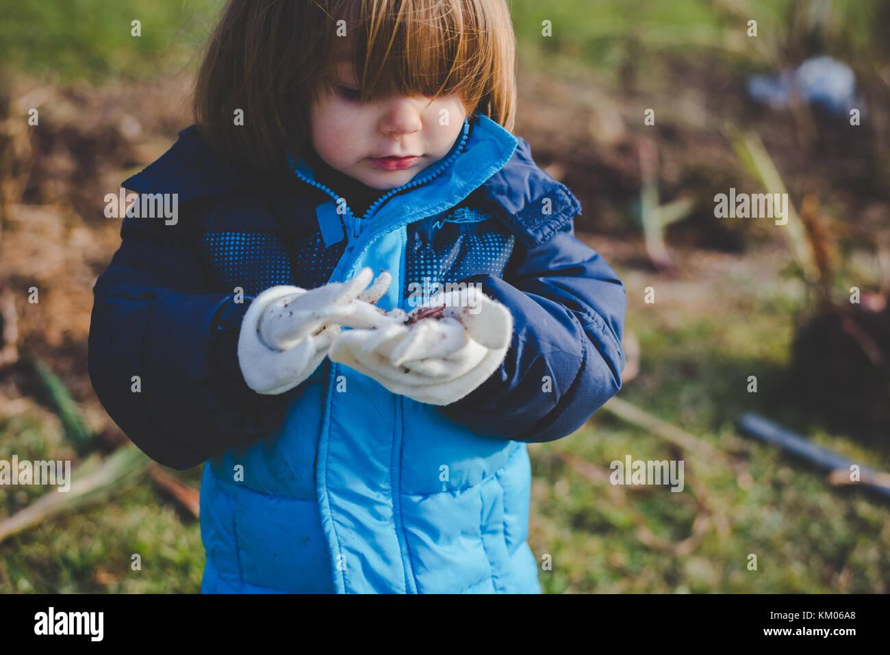 Une petite fille à la saleté à dans ses mains couvertes de gants Banque D'Images