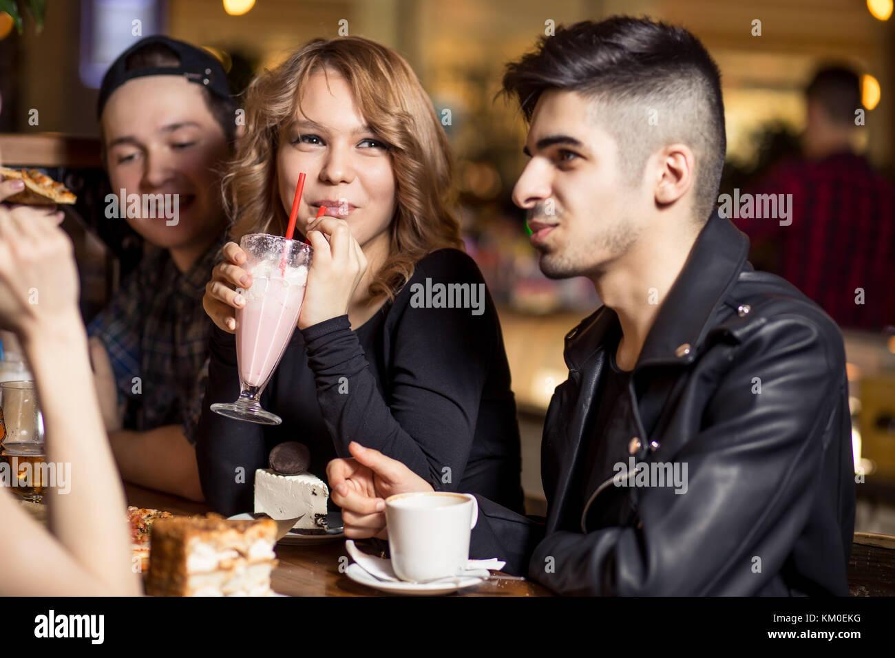Jeune femme à boire le lait frappé alors qu'il était assis avec des amis au café Photo Stock