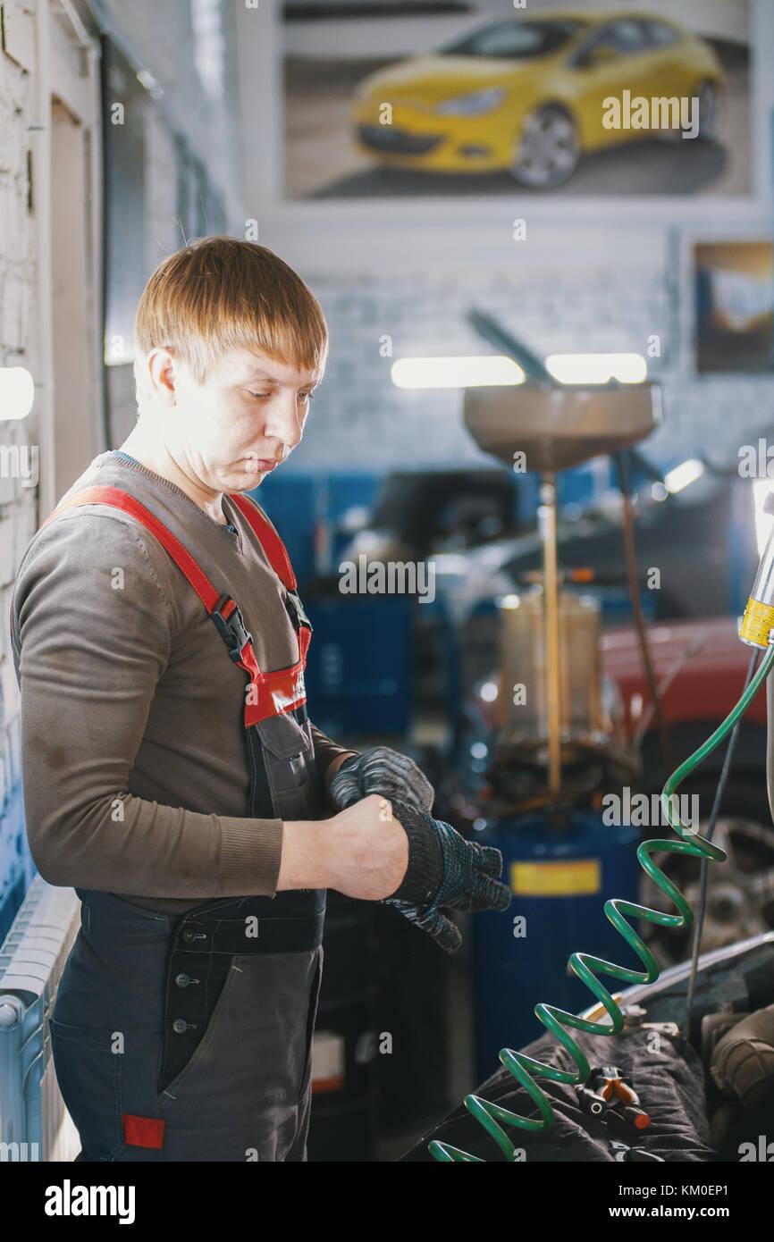 Mécanicien travaille avec voltmètre - Voiture électrique - câblage électrique Photo Stock