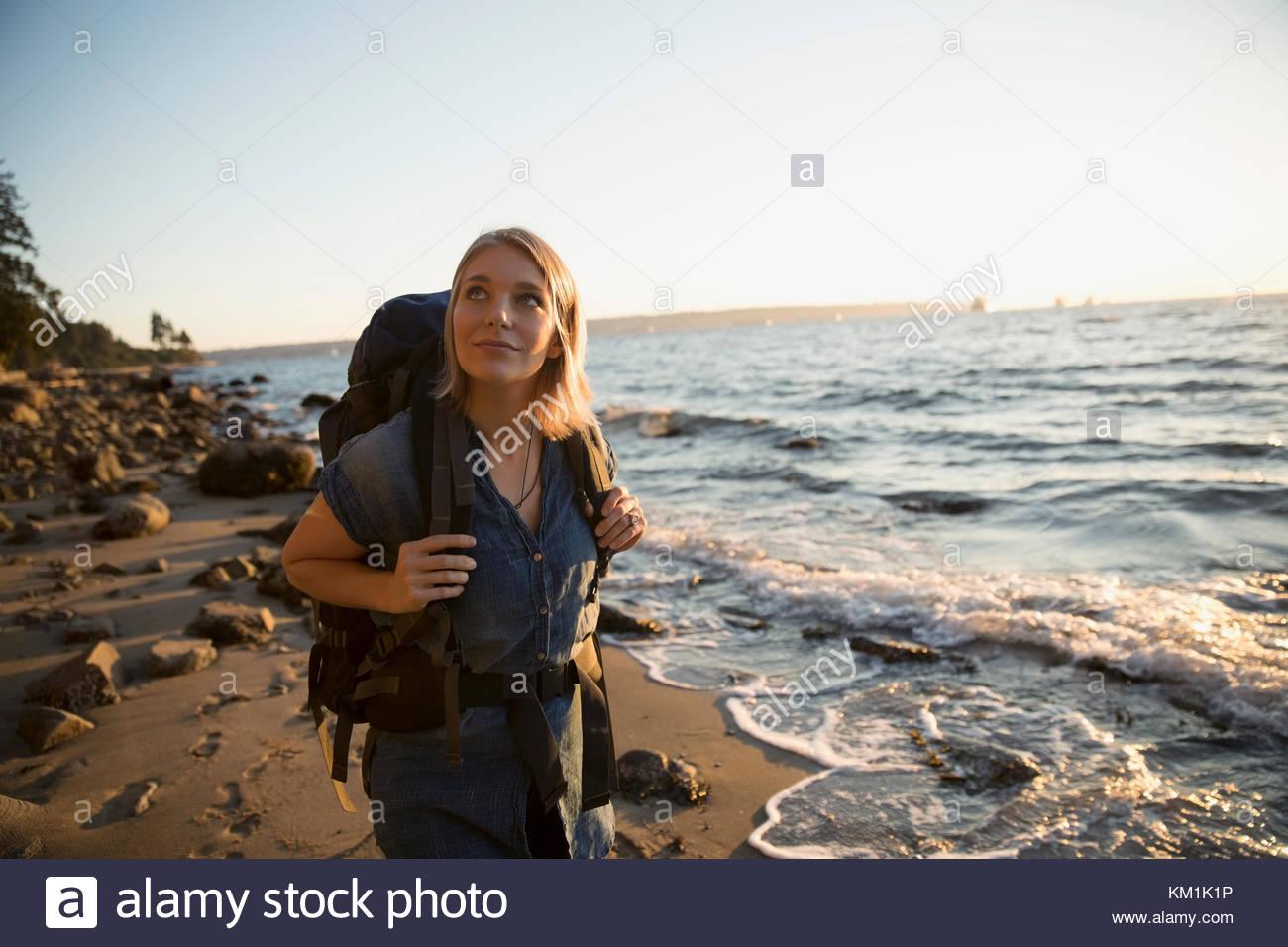Femme avec sac à dos de randonnée curieux jusqu'à la plage de l'océan au soleil Photo Stock