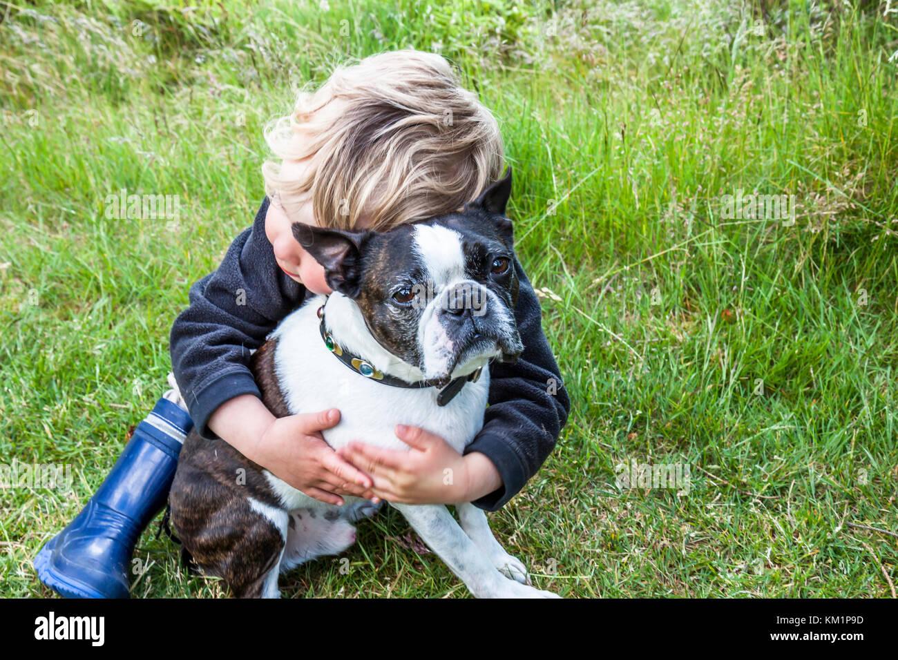 Avec amour de l'enfant et l'enveloppe avec précaution le pug dog Photo Stock