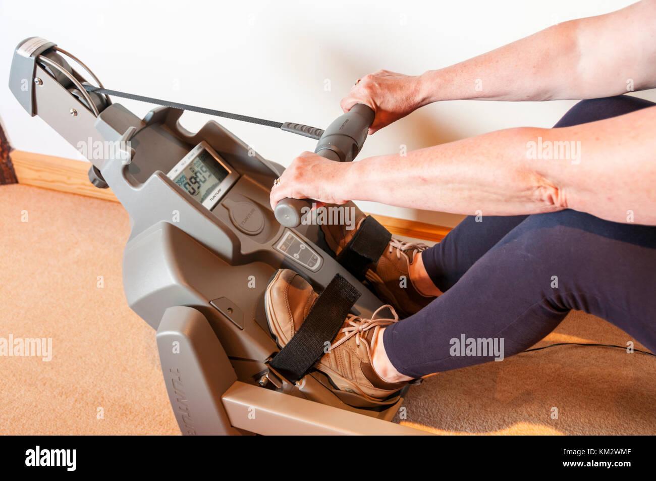 Femme à l'aide d'une machine d'exercice tunturi accueil. Photo Stock