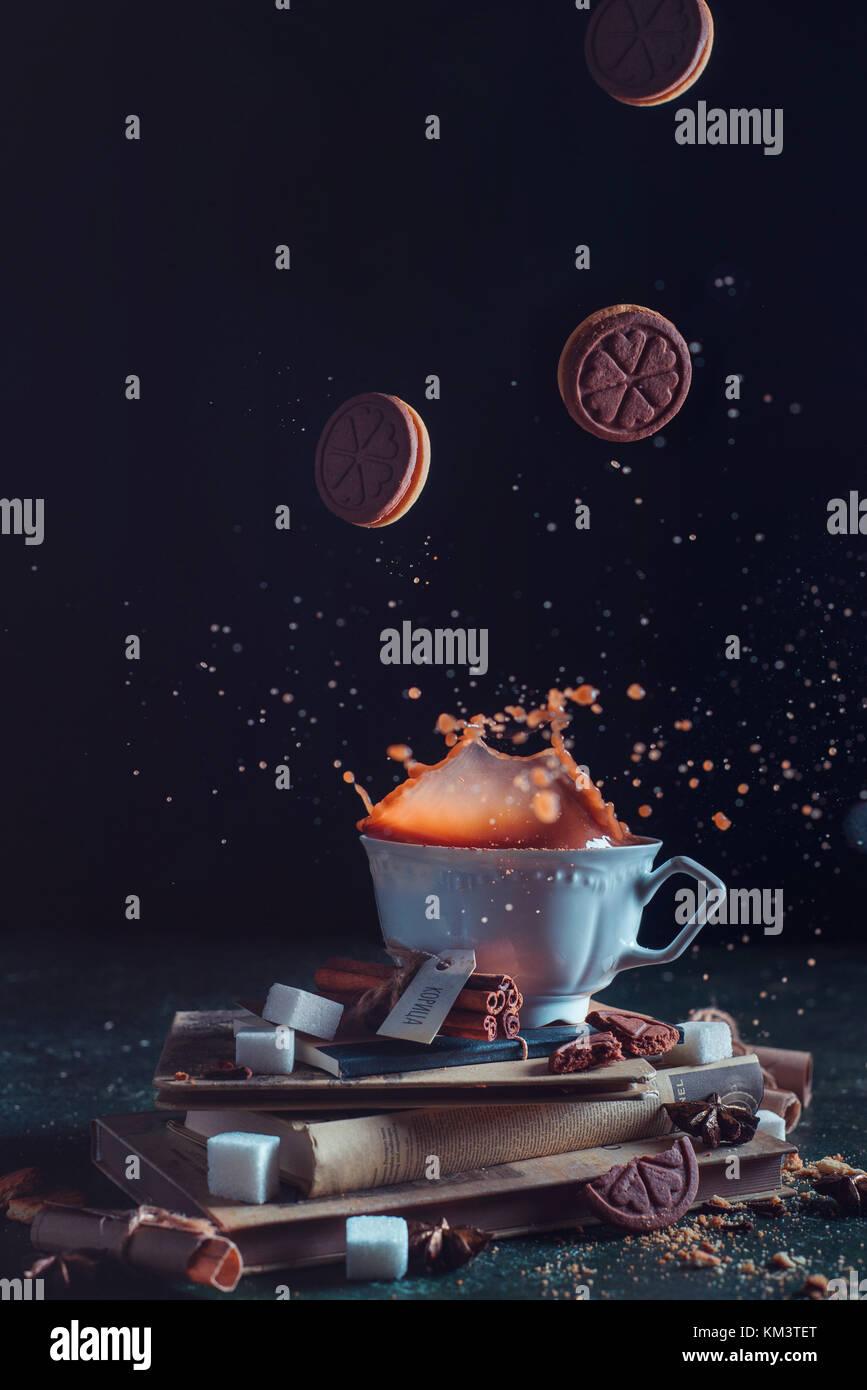 Tasse à thé en porcelaine avec la chute des cookies et une touche sur un fond sombre. Aliments surgelés Photo Stock