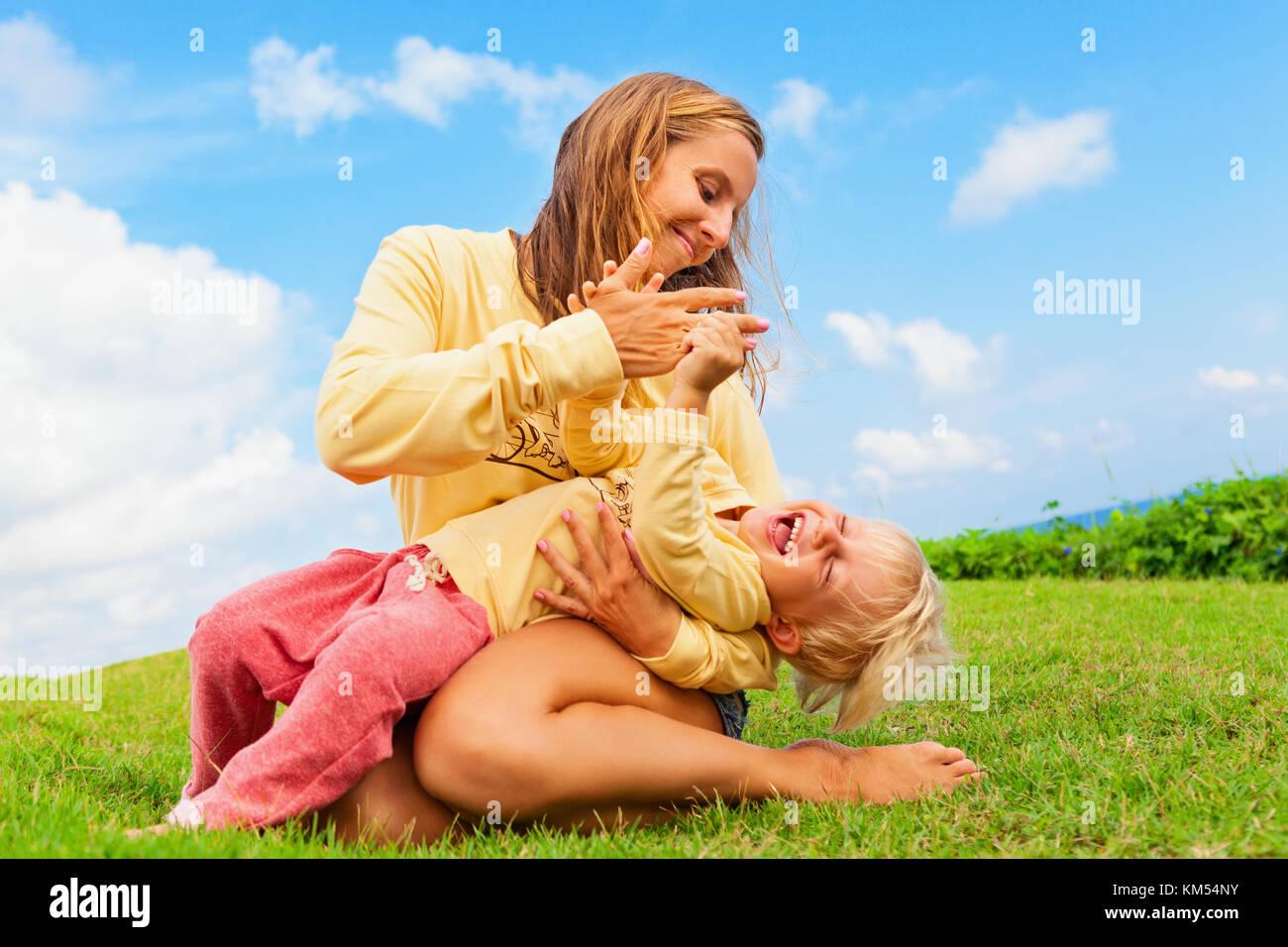 Famille heureuse sur l'herbe verte pelouse. enfant s'amuser sur l'extérieur de marche - mère Photo Stock