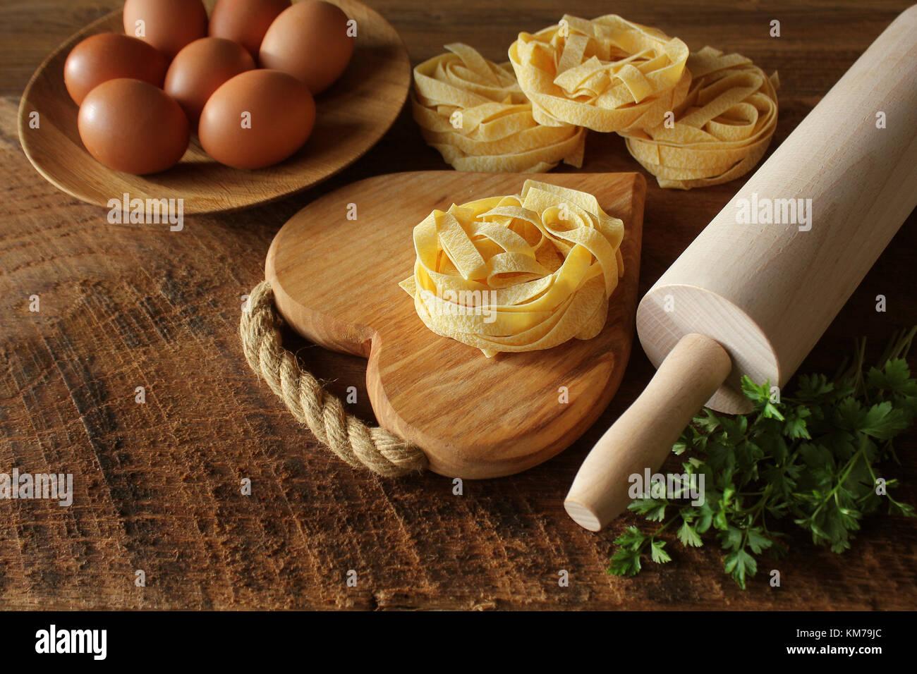 Les pâtes italiennes tagliatelles sur planche de bois et le rouleau à pâtisserie sur fond rustique. Photo Stock
