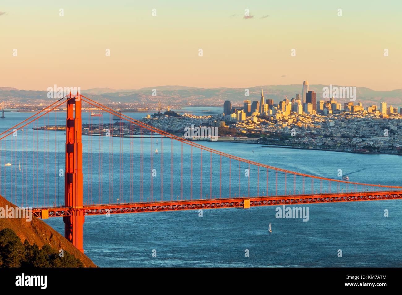 Le golden gate bridge, avec l'éclairage de la ville de San Francisco jusqu'au soir, la lumière Photo Stock