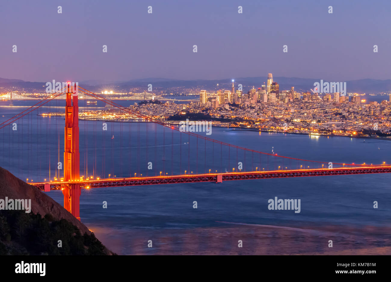 Golden Gate Bridge et de la ville de San Francisco s'allumer à la tombée de la nuit, en Californie, Photo Stock
