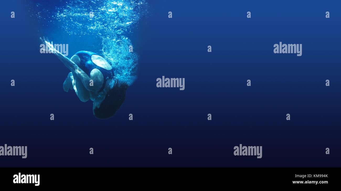 L'homme nage dans l'eau d'un bleu profond Photo Stock