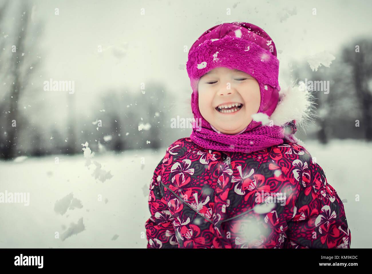 Enfant jouant avec des flocons de neige dans la forêt d'hiver Photo Stock