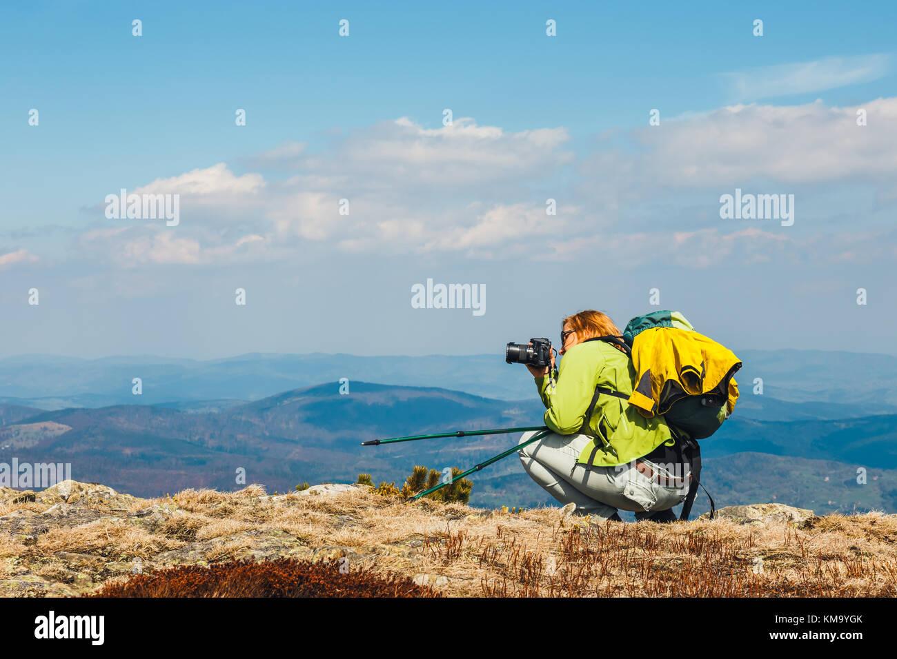 Femme assise sur la falaise et prend une photo Banque D'Images