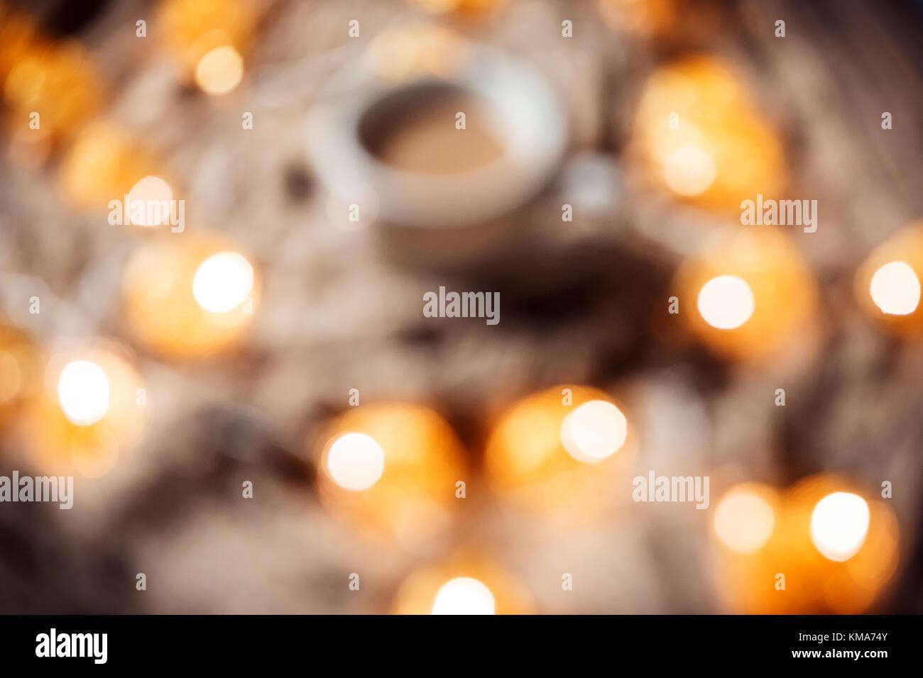 Noël arrière-plan flou avec un bokeh flou et golden garland tasse de café  sur une écharpe tricot brun. Une belle maison de vacances idée de postcar 3bf61419821