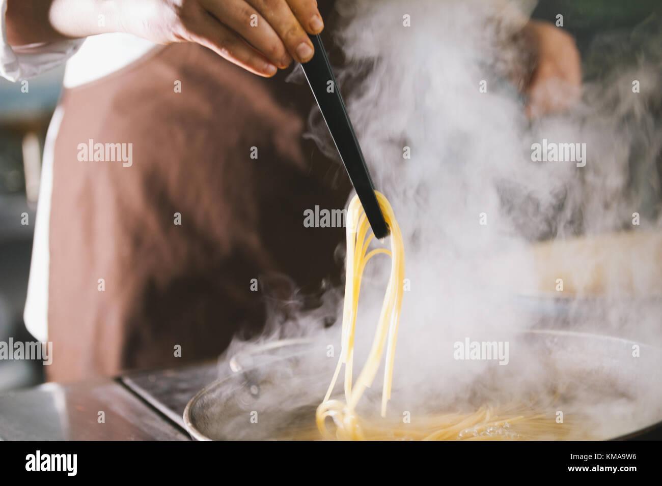 Chef cooking spaghetti dans restaurant Photo Stock