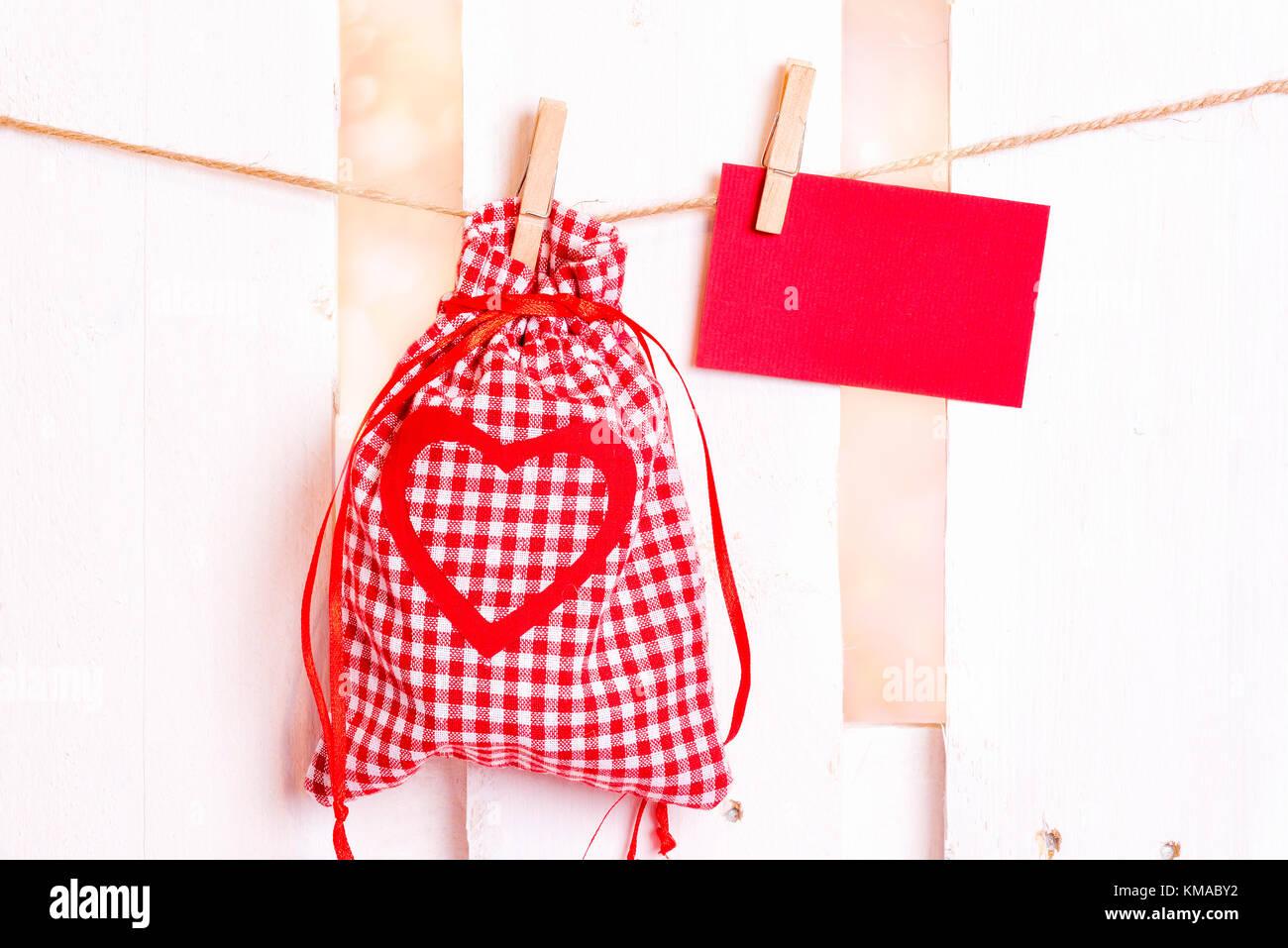 Thème de cadeaux d'image avec une pochette en tissu à carreaux décoratifs et un cœur rouge et Photo Stock