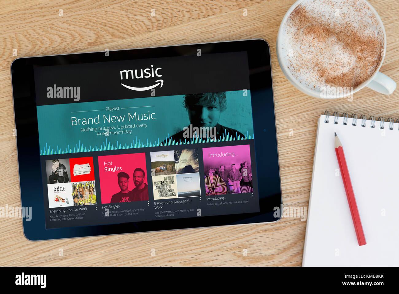 L'Amazon app Musique dispose sur un iPad tablet device qui repose sur une table en bois à côté Photo Stock