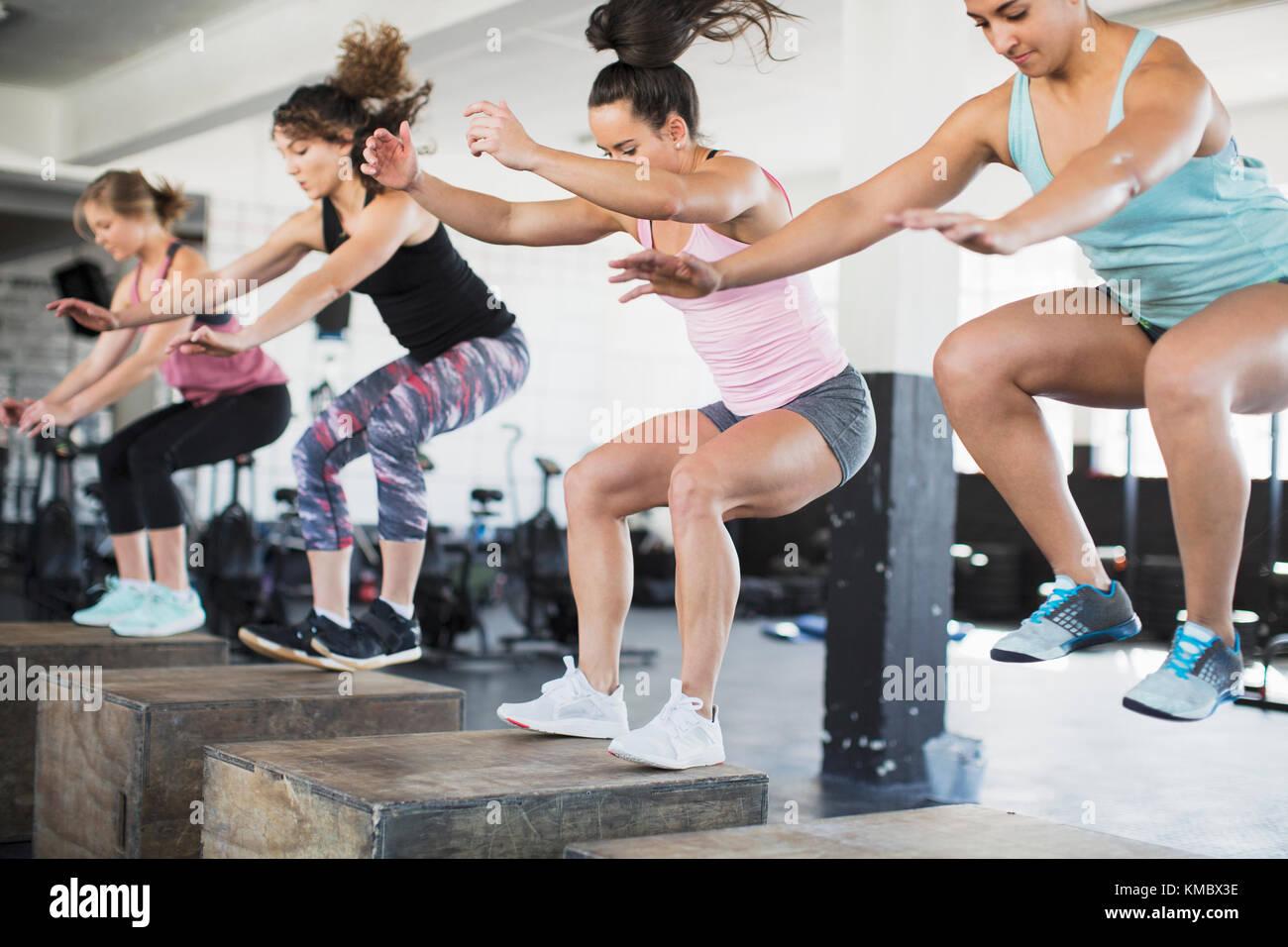 Femmes déterminées faisant sauter accroupi sur les cases de classe d'exercice Photo Stock