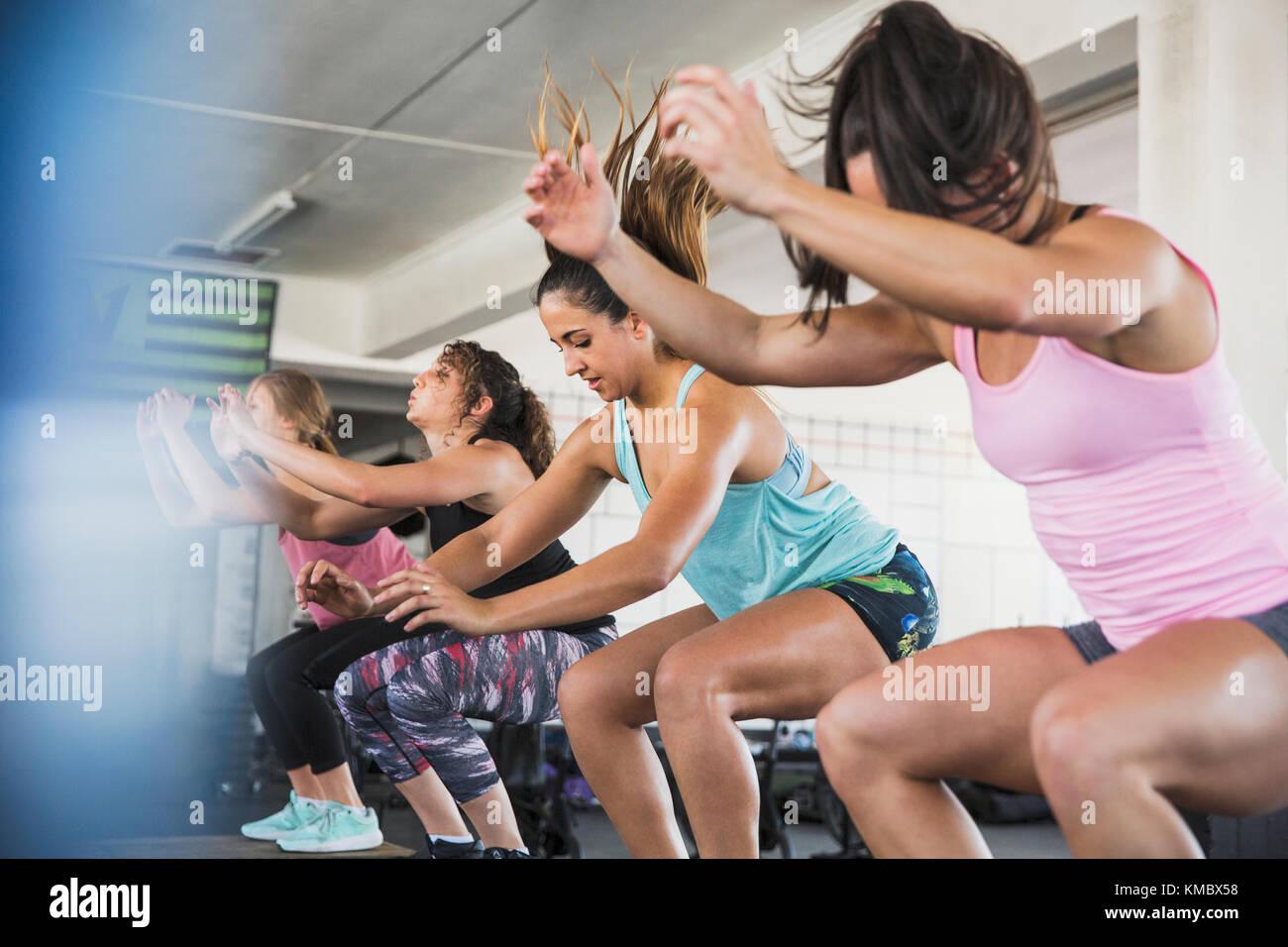 Les jeunes femmes faisant sauter accroupi en classe d'exercice Photo Stock