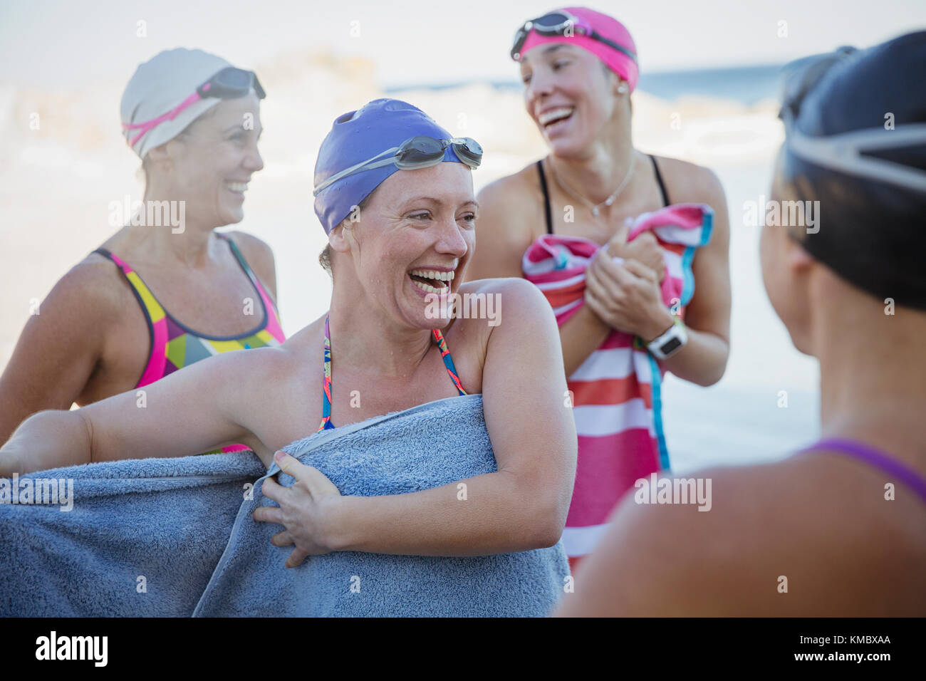 Les nageurs en eau libre de rire sécher avec des serviettes Photo Stock