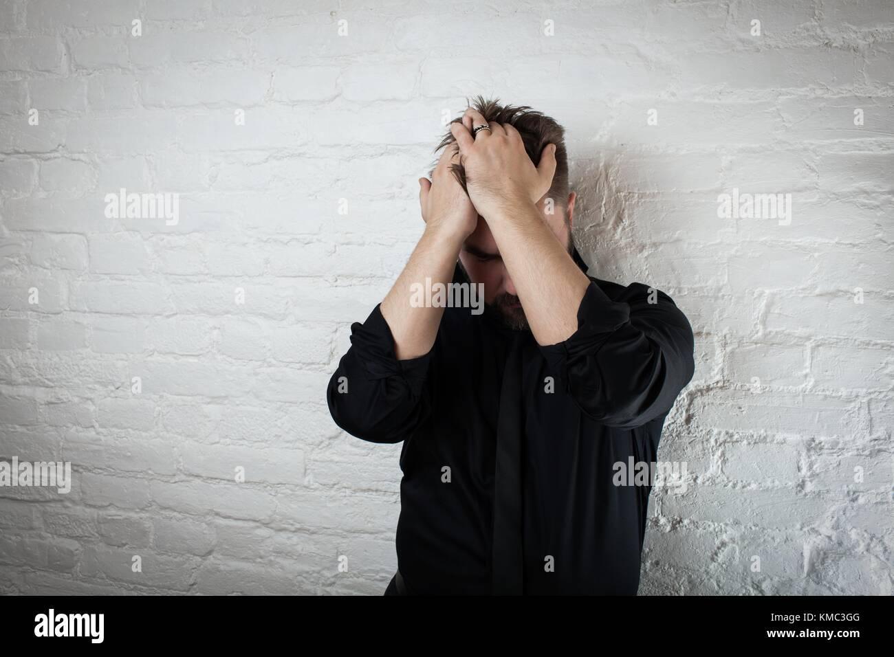 L'homme abattu tient sa tête alors qu'il souffre de dépression et l'échec. l'utiliser Photo Stock