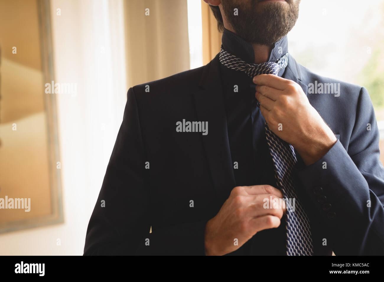Homme portant sa cravate à la maison Photo Stock