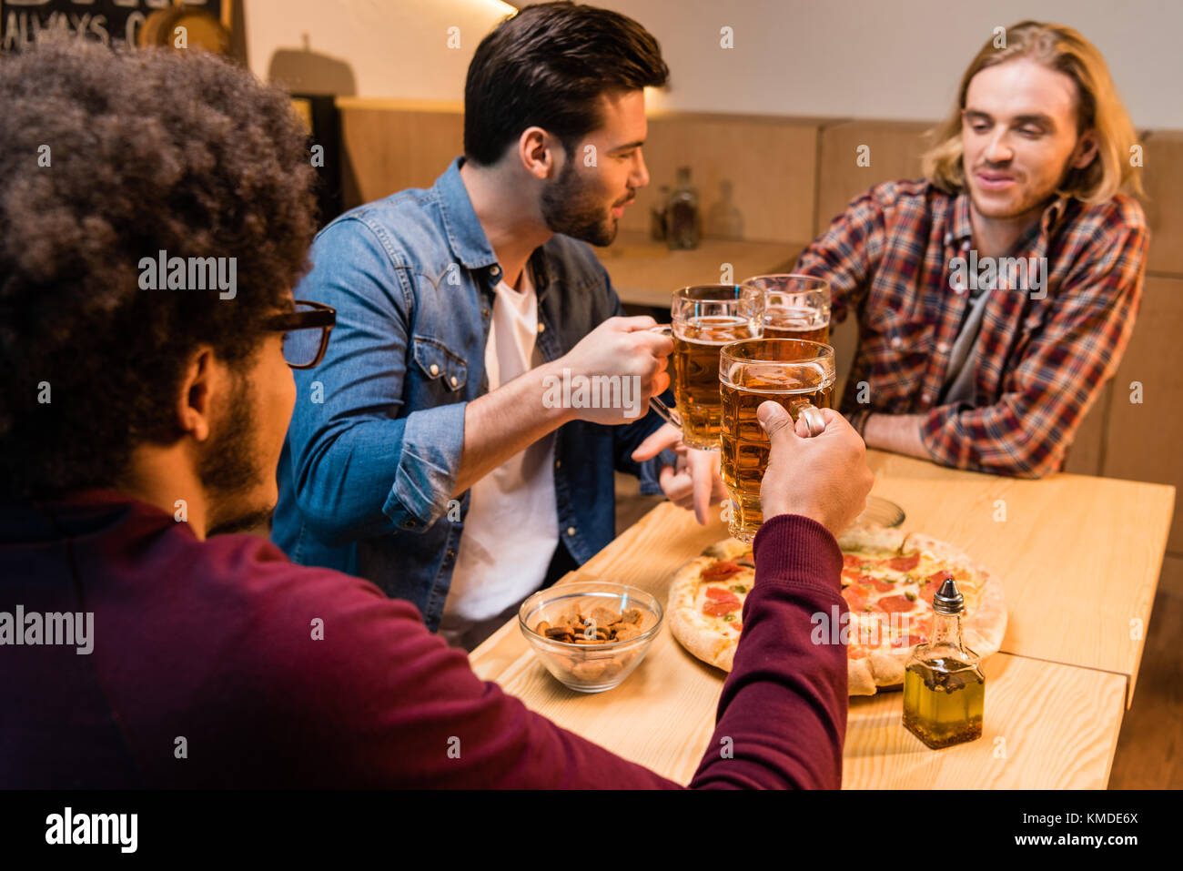 Les amis de pizza et de la bière en bar Photo Stock